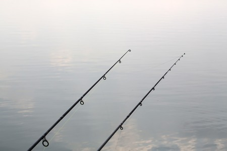 sportfishing: Two carbon fishing rods on background of smooth surface of water tranquility relaxation calm nature outdoor on natural background, horizontal picture