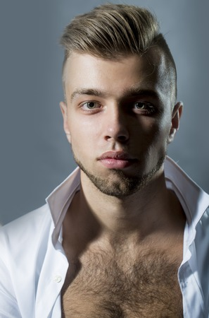 young unshaven: Portrait closeup of one young handsome sensual unshaven bearded man model with plush lips looking forward in studio on black background unbuttoned, vertical picture Stock Photo