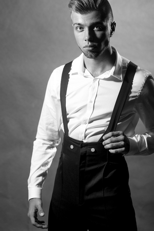 young unshaven: One young handsome sensual unshaven bearded man looking at camera with unbutton collar keeping his shirt stays foward in studio on black background black and white, vertical picture Stock Photo