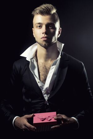 popped: One young handsome sensual unshaven bearded man looking at camera with popped unbutton collar white shirt black jacket keeping pink presentation box with bow stays forward in studio on black background, vertical picture Stock Photo