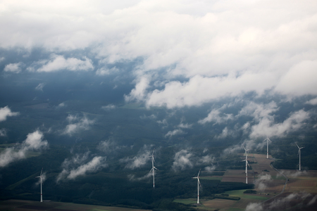 windfarm: Panorama spectacular skyline view of cloudy blue sky from airplane window over windfarm landscape background wind turbines renewable power energy stations, horizontal picture