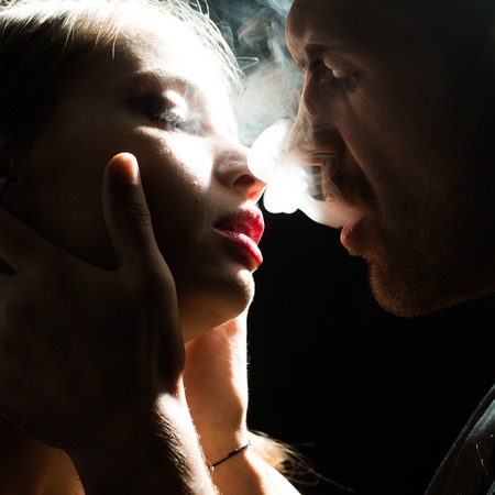 Passionate couple vis-?-vis bearded man puffing smoke into face of beautiful young woman with eyes closed in studio play of light and shadow on dark background, square picture