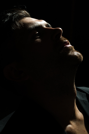 males: Dark portrait closeup of one young handsome sensual unshaven bearded man model half face stares ahead in studio play of light and shadow on black background, vertical picture