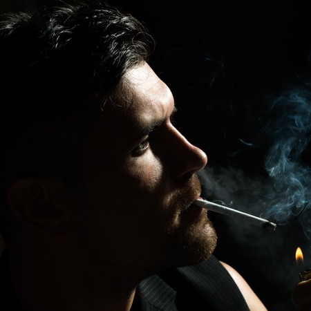 Dark portrait closeup of one young handsome sensual unshaven bearded man model half face lights up cigarette stares ahead in studio play of light and shadow on black background, square picture