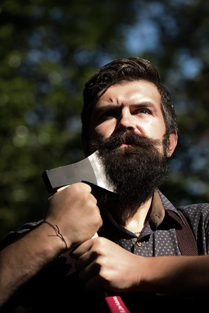 cut: Portrait of one handsome strong stylish male logger of young serious man with long lush black beard and moustache in shirt holding wooden axe standing sunny day outdoor on natural background, vertical