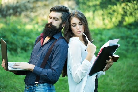 green office: Business young pair of slim woman and man with long lush black beard with office devices of laptop glasses mobile phone paper folder and standing outdoor on green grass, horizontal photo