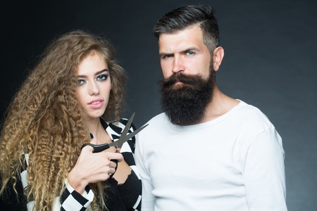 looking forward: Couple of long-haired young beautiful woman holding scissors with handsome bearded gray-haired man with moustache looking forward on grey background, horizontal picture