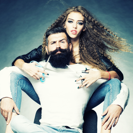 scissors: Couple of long-haired young beautiful woman holding two pairs of scissors sitting behind handsome bearded grey-haired man with moustache both looking forward on grey background, square picture Stock Photo