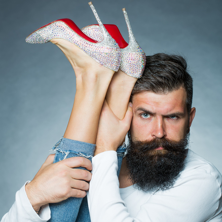 boy long hair: Portrait closeup of handsome grey-haired unshaven man with long beard moustache eyebrow raised holding legs of woman in jeans diamante high heels posing in studio on grey background, vertical picture Stock Photo