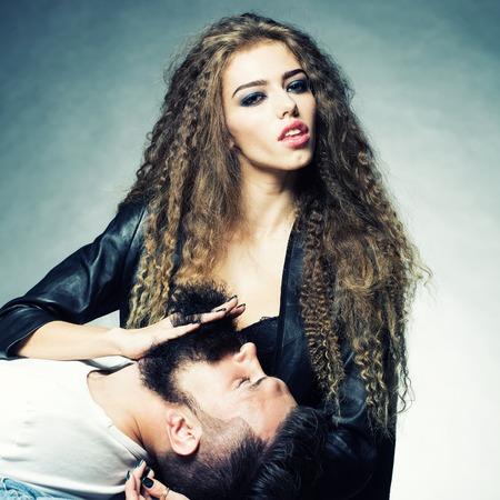 modelos hombres: Retrato pareja cerca de la hermosa mujer que se ejecutan a trav�s de los dedos la barba del hombre con el bigote acostado boca arriba sobre fondo gris, imagen cuadrada joven de pelo largo