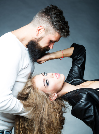 sensual couple: Portrait closeup couple of long-haired young sensual woman back arched touching beard of man with moustache bent over girl face holding hair grey background, vertical picture Stock Photo