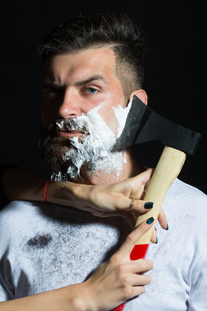 hatchet man: Portrait closeup young handsome sensual bearded man having shaved scrape chin with chopper foam frown studio play of light and shadow on black background, vertical picture