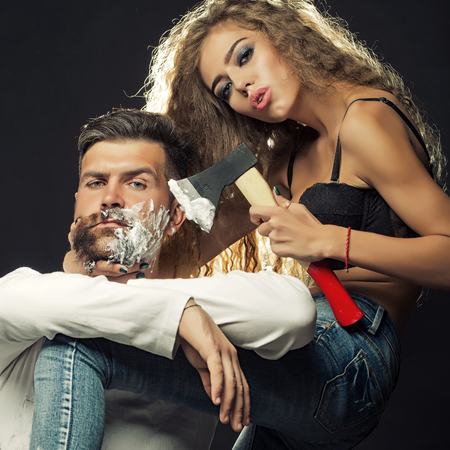 severity: Portrait closeup couple of long-haired young sensual woman shaving handsome bearded grey-haired man with chopper and foam looking forward on grey background, square picture