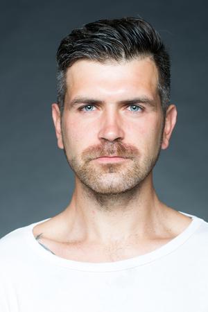 Portret close-up van een knappe sensuele geschoren man met haren en wenkbrauwen opgeheven model naar uit in de studio op een grijze achtergrond, verticale foto