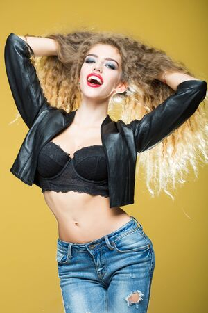 sexy bra: Attractive radiant looking blond young woman lifting her wavy long hair with hands wearing black leather jacket underwire bra jeans posing in studio on yellow background, vertical picture