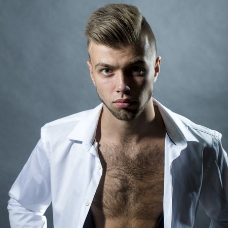 young unshaven: Portrait closeup of one young handsome sensual unshaven bearded man model with plush lips looking forward in studio on black background unbuttoned, square picture