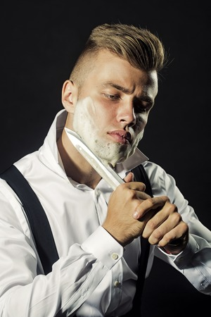 unbutton: One young handsome sensual man shaving his face with knife and foam looking at camera with unbutton collar keeping his shirt stays in studio on black background, vertical picture Stock Photo