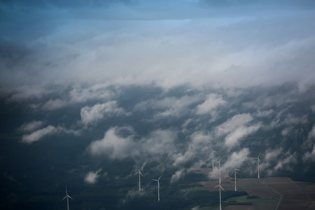 farm landscape: Panorama spectacular skyline view of cloudy blue sky from airplane window over windfarm landscape background wind turbines renewable power energy stations, horizontal picture