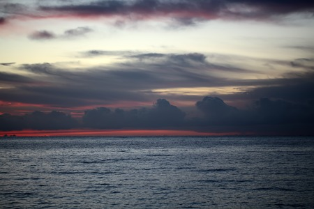rosy: Magic evening seascape view on closeup calm blue waterways of see with bright red and blue horizon line under bright dark and light red rosy and blue sky with low cloud cover, horizontal picture