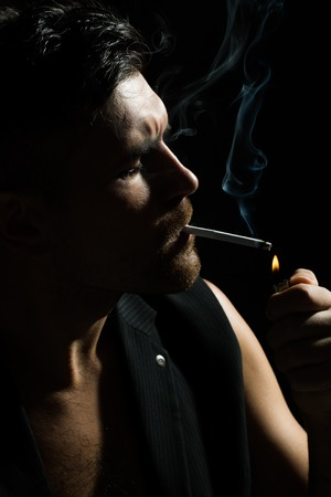 young unshaven: Portrait closeup young handsome sensual unshaven bearded man model half face wearing waistcoat next to skin lights up cigarette studio play of light and shadow on black background, vertical picture