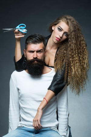 looking forward: Couple of long-haired young beautiful woman holding scissors smuggled into handsome bearded grey-haired man with moustache sitting looking forward on grey background, vertical picture Stock Photo