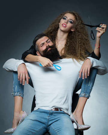 looking forward: Couple of long-haired young beautiful woman holding two pairs of scissors sitting behind handsome bearded grey-haired man with moustache both looking forward on grey background, vertical picture Stock Photo