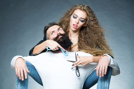 looking forward: Couple of long-haired young beautiful woman holding two pairs of scissors sitting behind handsome bearded grey-haired man with moustache both looking forward on grey background, horizontal picture Stock Photo