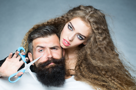 eyebrow raised: Portrait closeup couple of long-haired young beautiful woman holding scissors trying to cut long beard of grey-haired man with moustache and eyebrow raised on grey background, horizontal picture Stock Photo