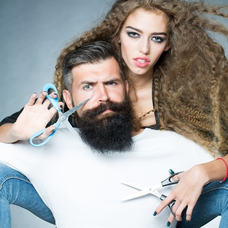 eyebrow raised: Portrait closeup couple of long-haired young beautiful woman holding scissors trying to cut long beard of grey-haired man with moustache and eyebrow raised on grey background, square picture