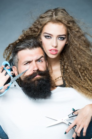 hair cut: Portrait closeup couple of long-haired young beautiful woman holding scissors trying to cut long beard of grey-haired man with moustache and eyebrow raised on grey background, vertical picture Stock Photo