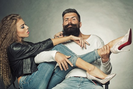 beard woman: Couple sitting on chairs young woman wearing black leather jacket jeans diamante high heels pulling beard of unshaved man he playing legs of girl like guitar on grey background, horizontal picture Stock Photo