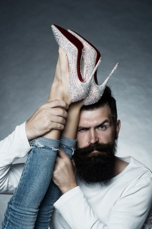diamante: Portrait closeup of handsome grey-haired unshaven man with long beard moustache eyebrow raised holding legs of woman in jeans diamante high heels posing in studio on grey background, vertical picture Stock Photo