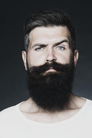 hombre con barba: Retrato del primer de un hombre guapo sensual de pelo gris sin afeitar bronceada con una larga barba y bigote modelo ganas en el estudio, imagen vertical blanco y negro