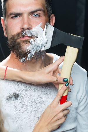 to scrape: Portrait closeup young handsome sensual bearded man having shaved scrape chin with chopper foam frown studio play of light and shadow on black background, vertical picture
