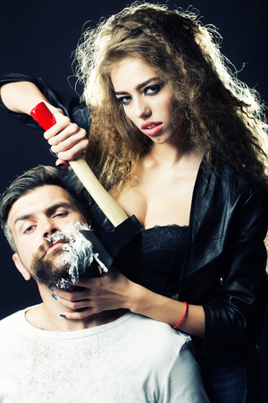 looking forward: Portrait closeup couple of long-haired young sensual woman shaving handsome bearded grey-haired man with chopper and foam looking forward on grey background, vertical picture