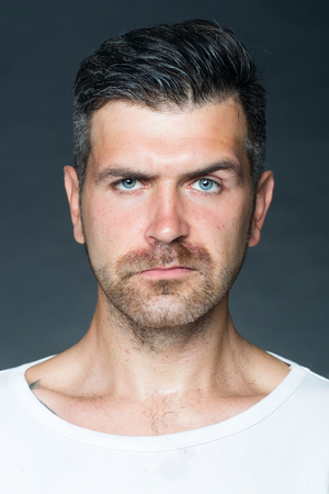 eyebrow raised: Portrait closeup of one handsome sensual shaved man with  bristle and eyebrow raised model looking forward in studio on grey background, vertical picture