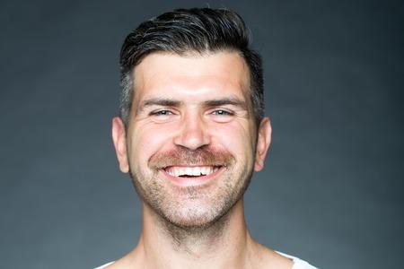 sonrisa: Retrato de cerca de un hombre afeitado sensual guapo con cerdas sonriendo andl mirando hacia adelante en el modelo de estudio posando sobre fondo gris, horizontal de la imagen