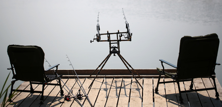 arm chairs: Two arm chairs standing on pier and four fishing spinning rods on support near pond with wooden pier male hobby recreation at summertime outdoor on natural background, horizontal picture