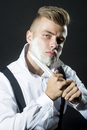 stays: One young handsome sensual man shaving his face with knife and foam looking at camera with unbutton collar keeping his shirt stays in studio on black background, vertical picture Stock Photo