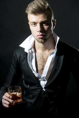 neckband: Portrait of one young handsome stylish young man in white sgirt and black jacket holding glass with alcohol drink in studio background, vertical picture