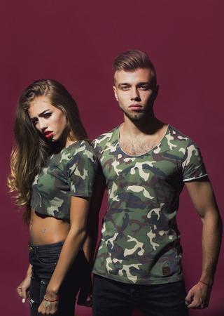 upper half: Portrait of bold cool sexual attractive charming fearless young couple models dressed in fashion camouflage style t-shirts looking straight posing on purple background studio, vertical picture Stock Photo