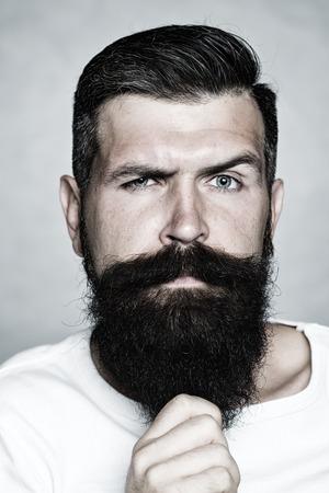 Portrait gros plan d'un bel homme mal rasé aux cheveux gris tirant longue barbe avec moustache et sourcils modèle soulevées hâte en studio en noir et blanc sur fond, image verticale Banque d'images - 47323987
