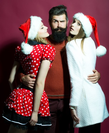 One man with long beard embracing two new year young weman with curly hair in red santa claus hat celebrating christmas standing on studio purple background, vertical picture