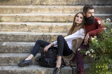 romaans: Een mooie stijlvolle paar jonge vrouw en senior man met lange zwarte baard zitten omarmen dicht bij elkaar buiten in de herfst straat op trappen zonnige dag, horizontaal beeld