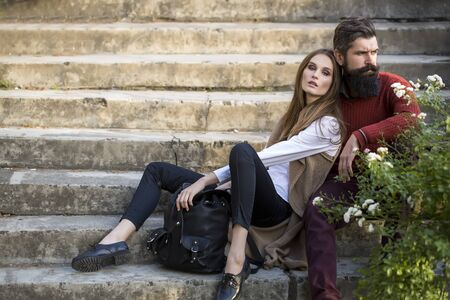 romance: One beautiful stylish couple of young woman and senior man with long black beard sitting embracing close to each other outdoor in autumn street on stairs sunny day, horizontal picture