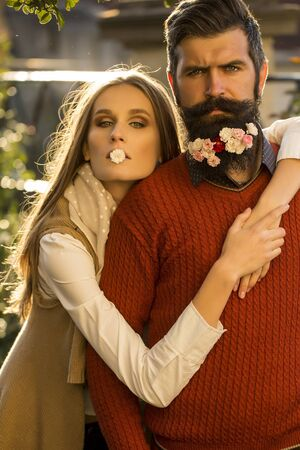 flowers boy: Young beautiful couple of woman embracing man with long black beard with many little white red and pink flowers sunny day outdoor on natural background, vertical picture Stock Photo