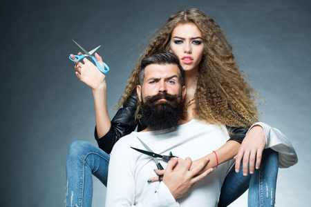 Couple of long-haired young beautiful woman holding two pairs of scissors sitting behind handsome bearded grey-haired man with moustache both looking forward on grey background, horizontal picture Stock Photo