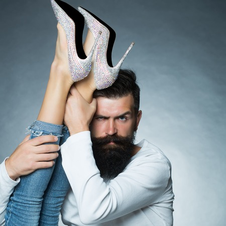 eyebrow raised: Portrait closeup of handsome grey-haired unshaven man with long beard moustache eyebrow raised holding legs of woman in jeans diamante high heels posing in studio on grey background, vertical picture Stock Photo