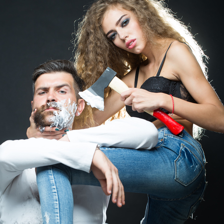 looking forward: Portrait closeup couple of long-haired young sensual woman shaving handsome bearded grey-haired man with chopper and foam looking forward on grey background, square picture