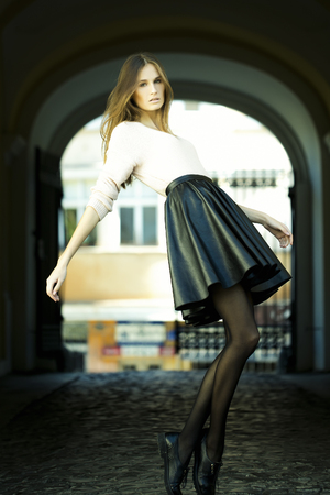 Full length view of one beautiful sensual straight slim young fashionable girl with blonde lush long hair legs and black leather skirt standing near street arch on outdoor background, vertical picture